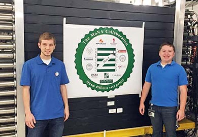 Two students pose for photo at National Superconducting Laboratory in Michigan