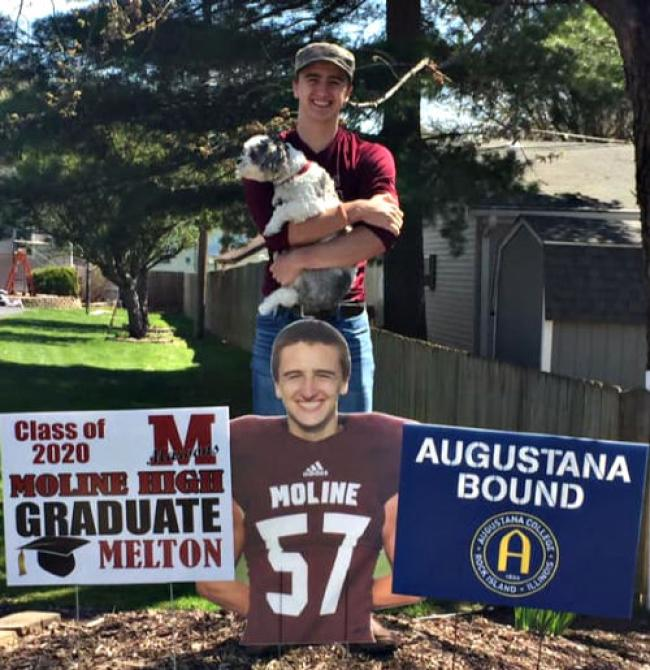 John standing behind 3 signs. One of the signs is a photo of him in a maroon football jersey